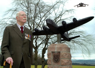 Flying Officer PJS Boggis with the Stirling Bomber Statue